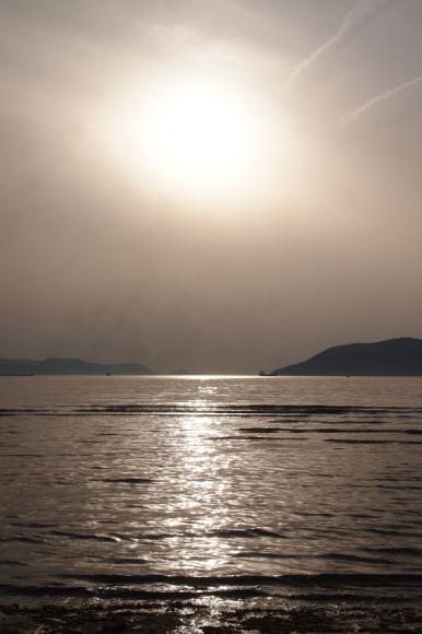 暮れゆく日に染まる初夏の海の写真。