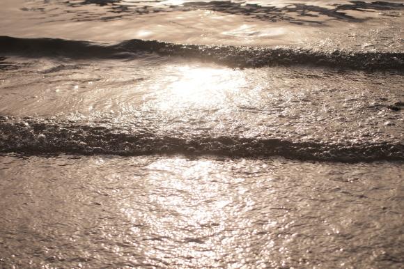 初夏の海辺で夕日にきらめく波と水面の写真。