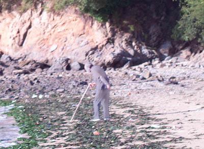 浜辺で杖をついてヨロヨロしながら何かを探している様子のおじいさん。
