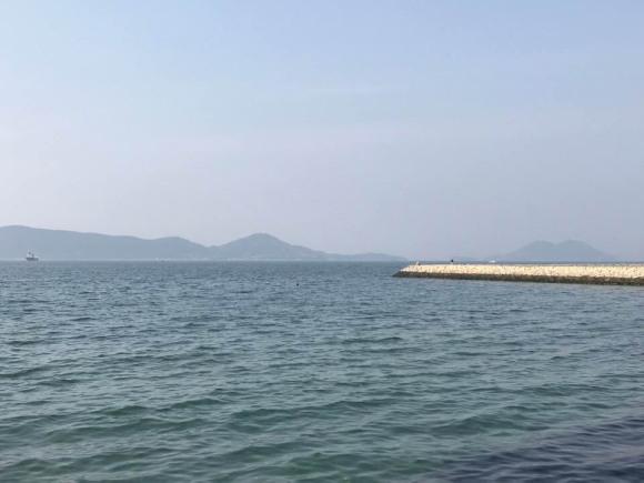 岸壁で釣りをする人、うっすらと霞んで見える島々の写真